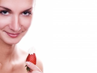 Beautiful young naked girl with red juicy strawberry
