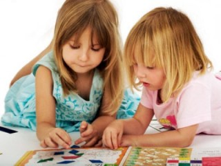 Two sisters play an educational game. --- Image by © Martin Harvey/Corbis